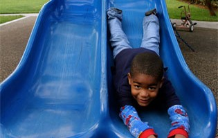 young homeless boy on slide