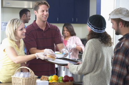 People serving food in homeless shelter